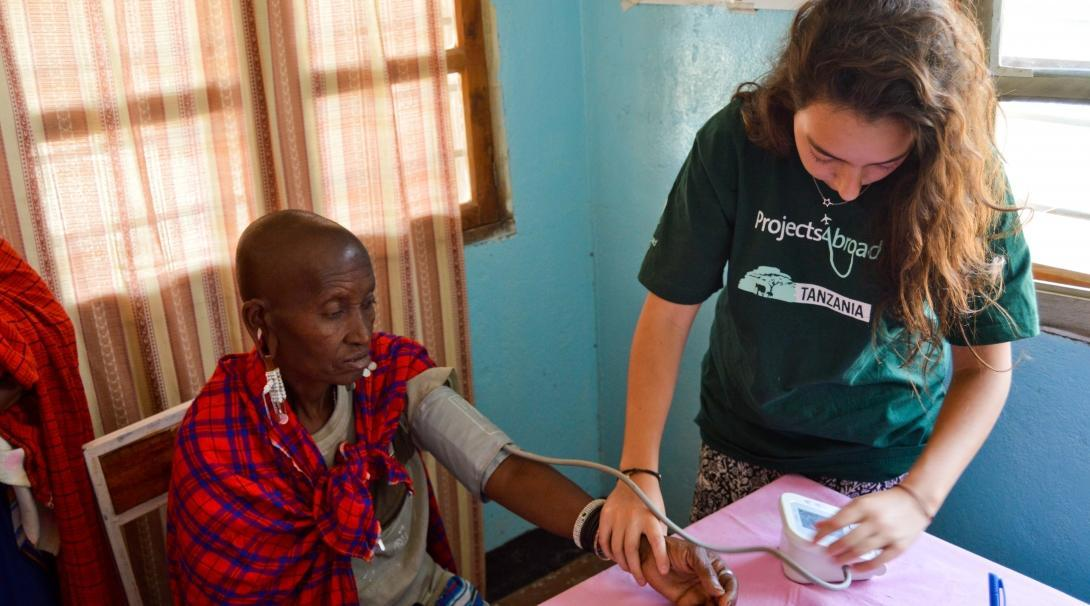 Projects Abroad intern takes the blood pressure of local residents during her medicine internship in Tanzania.
